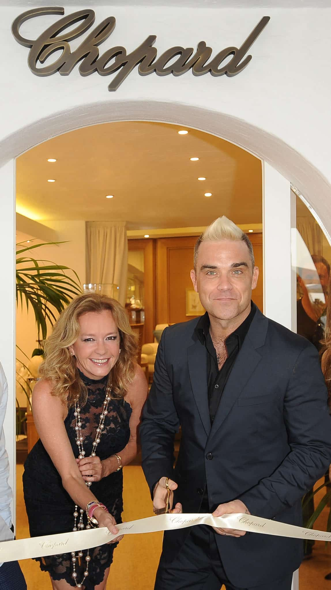 Caroline Scheufele and Robbie Williams cutting the ribbon for the boutique opening in 2015